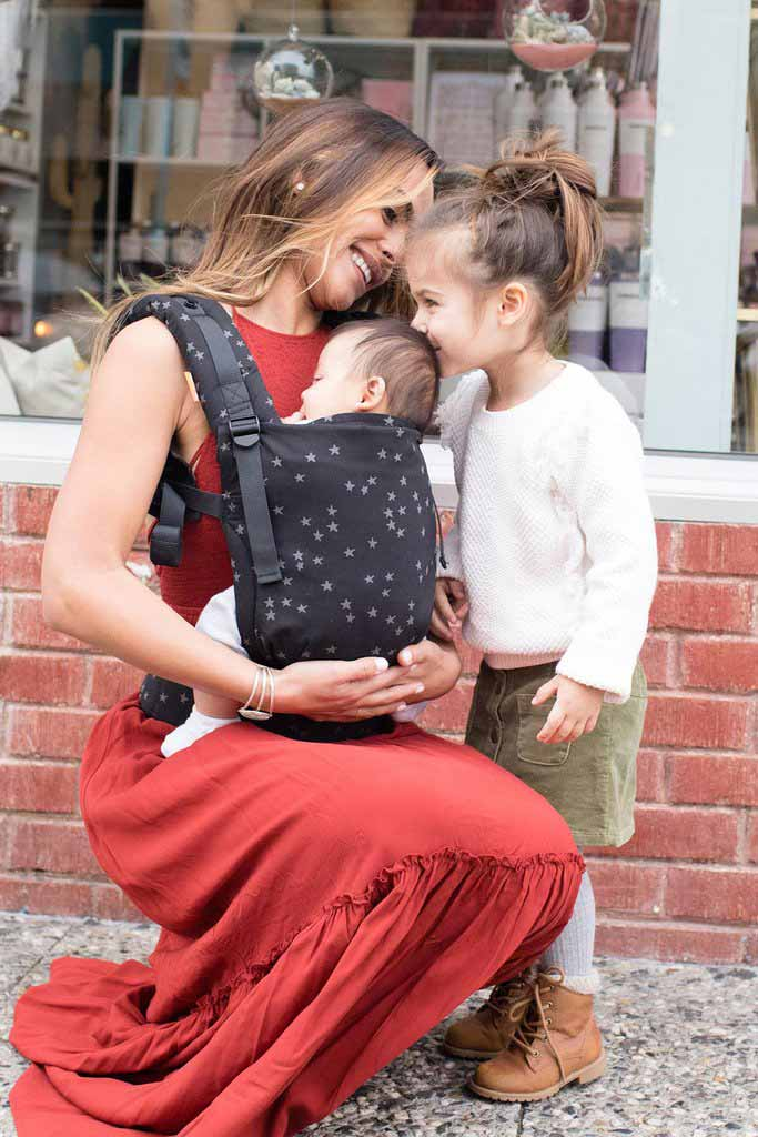 A woman in a red dress carrying her baby in a Tula Free To Grow Discover baby carrier, bending down to allow her toddler daughter to kiss the top of the baby's head.