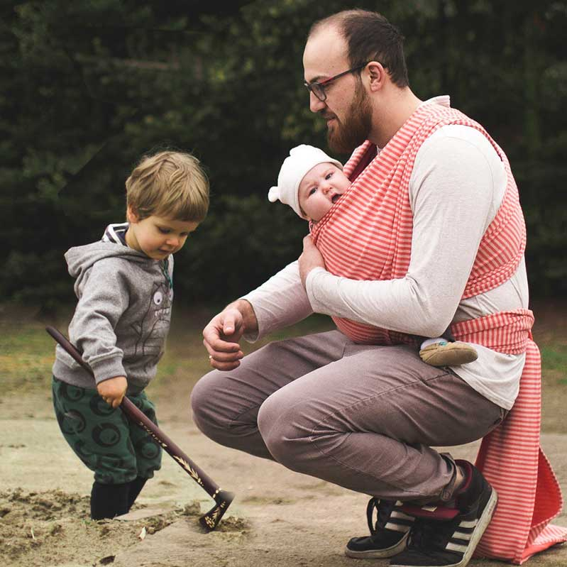 A man playing with his toddler son in the sand whilst carrying his baby in a red and white Didymos wrap